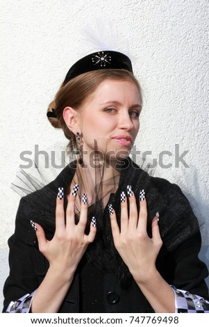 Stylish girl with black fan in the hands of transparent tulle, with a manicure in the tone of the cuffs on the sleeves: black-and-white checkered.