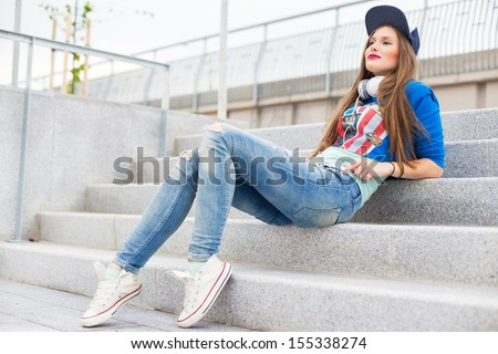 Stylish girl with headphones, long hair and jeans sitting on steps