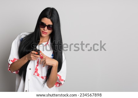 Stylish girl with long black hair uses a cell phone. Girl twenty-six years. - stock photo