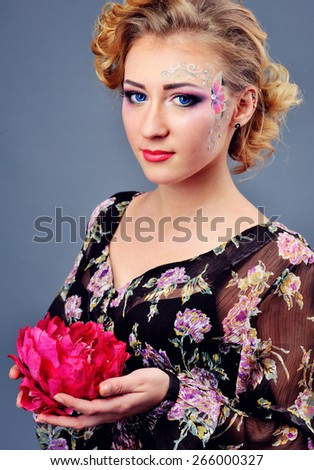 stylish glamor girl with beautiful hairstyle and bright makeup keep flowers