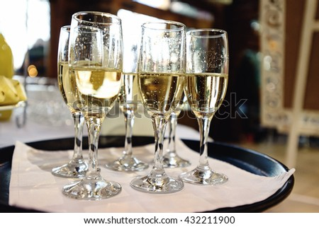 stylish glasses with champagne on tray, alcohol bar at luxury wedding reception, catering in restaurant - stock photo