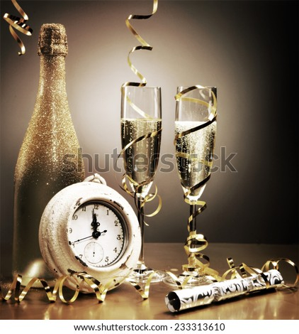 Stylish gold still life depicting the countdown to midnight on New Years Eve with a clock, party cracker, streamers and flutes and a bottle of golden champagne to celebrate - stock photo