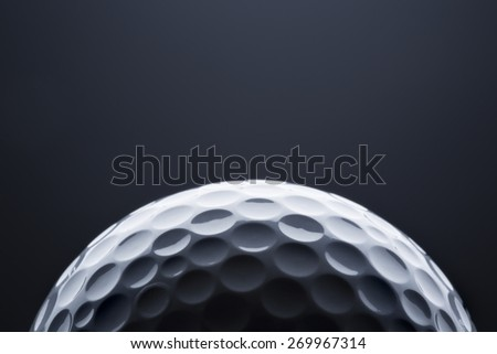Stylish golf ball isolated on empty dark blue background, close up shot with  blank space for text. - stock photo