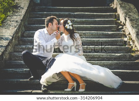 stylish gorgeous happy brunette bride  and elegant groom kissing on the background of an old stairs - stock photo