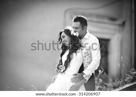 stylish gorgeous happy brunette bride  and elegant groom on the background of an old building