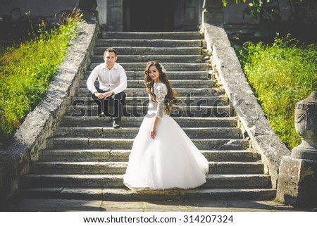 stylish gorgeous happy brunette bride  and elegant groom on the background of an old stairs - stock photo