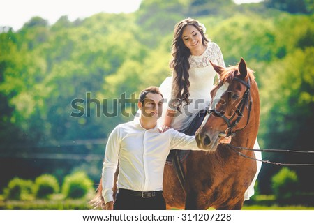 stylish gorgeous happy brunette bride riding a horse and elegant groom on the background of a park