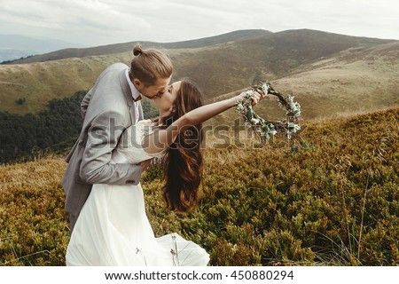 stylish groom  kissing gorgeous bride in sun light, perfect moment, boho wedding couple, luxury ceremony at mountains with amazing view - stock photo
