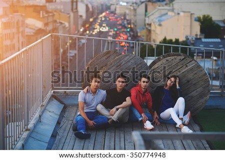 Stylish group of friends posing while sitting on a roof with evening city with lights machines on background, young trendy hipster boys and girl enjoying good time and leisure during theirs weekend   - stock photo