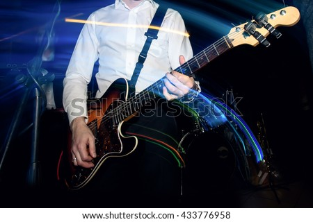 stylish guitarist playing on a stage with a band on wedding reception with cool motion light - stock photo
