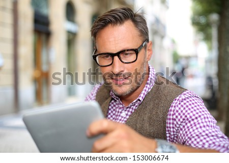 Stylish guy connected on internet with tablet in town - stock photo