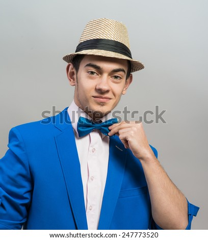 stylish guy in the hat and blue jacket dresses butterfly - stock photo