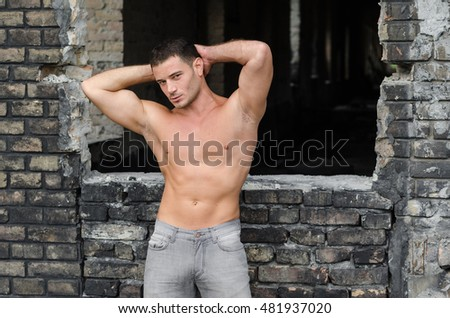 Stylish guy posing without shirts in front of the old warehouse