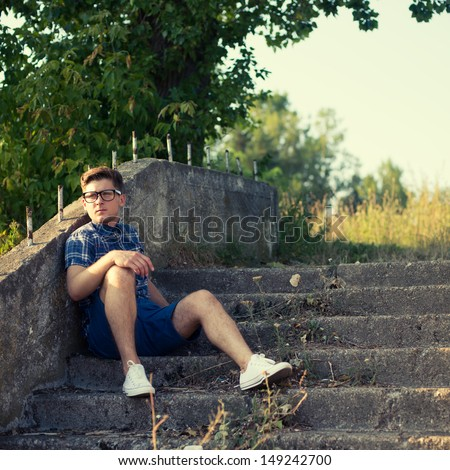 stylish guy with glasses sitting on the stairs