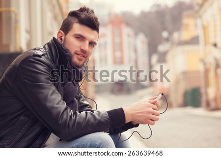 Stylish guy with smartphone in the city - stock photo