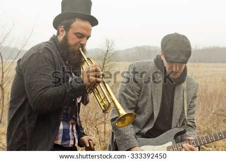 Stylish gypsies play trumpet and electric guitar on a wilderness path