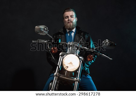 Stylish handsome bearded businessman waiting on his motorbike with a glowing headlamp looking at the camera with a serious expression, dark background - stock photo