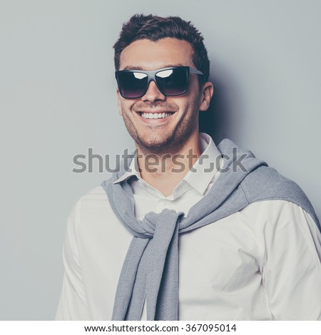 Stylish handsome. Confident young man wearing sunglasses and smiling while standing against grey background