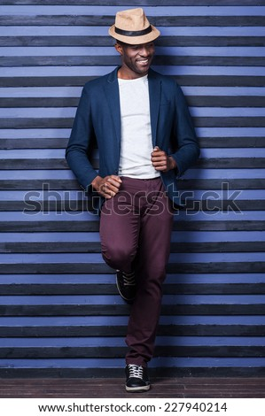 Stylish handsome. Full length of handsome young African man adjusting his jacket and smiling while standing against striped background - stock photo