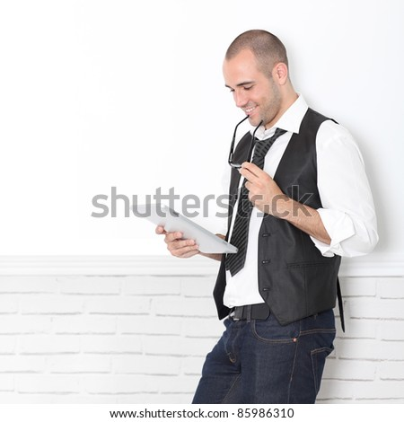 Stylish handsome guy leaning on wall with touchpad - stock photo