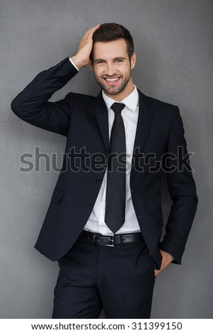 Stylish handsome. Smiling young businessman touching his hair and looking at camera while standing against grey background - stock photo