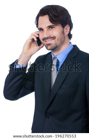 Stylish handsome young bearded businessman standing talking on his mobile phone listening to the conversation with a serious expression, isolated on white