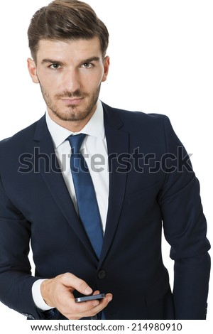 Stylish handsome young businessman chatting on his mobile phone listening to the call with a beaming smile of pleasure, isolated on white