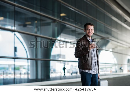 Stylish handsome young male traveller with bristle standing outdoors. Man wearing jacket and shirt. Smiling person looking to camera holding cup of coffee - stock photo