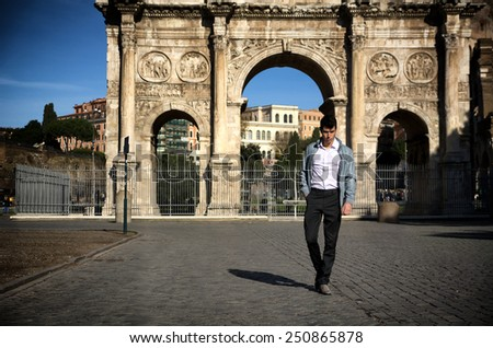 Stylish handsome young man walking in front of Arco di Costantino in Rome, Italy - stock photo