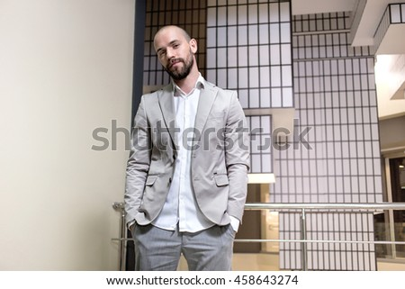 stylish handsome young man with with a beard standing indoors on  creative abstract background. Man wearing jacket, shirt
