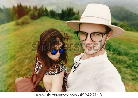 stylish  hipster couple traveling and smiling and having fun on top of mountains in summer, travel together concept, space for text