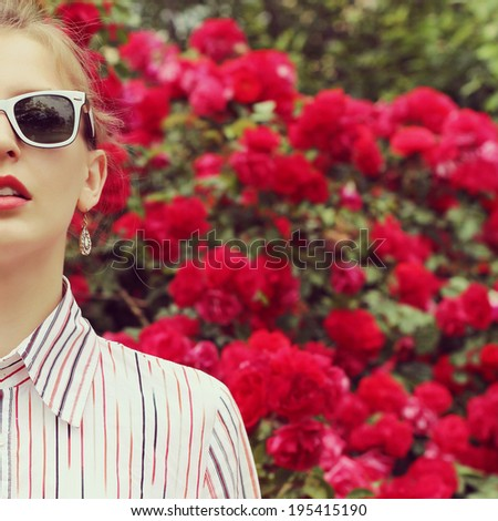 Stylish hipster girl in trendy glasses. Glamorous photo shoot in a chic outdoor garden. Photo toned style Instagram filters   - stock photo