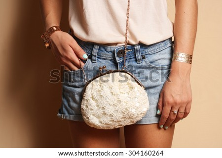 stylish hipster girl wearing cute trendy outfit jeans shorts with little bag and accessories Summer lifestyle fashion portrait  - stock photo