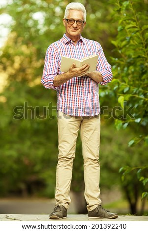 Stylish hipster grandpa concept. Portrait of smiling trendy handsome mature man with eyeglasses walking in the park and reading book. Fashionable casual clothing. Outdoor shot - stock photo