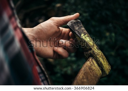 stylish hipster lumberjack with ax in the sunny forest in mountains - stock photo