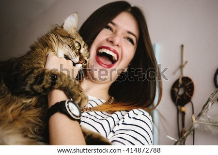stylish hipster woman playing with her cat in modern room - stock photo