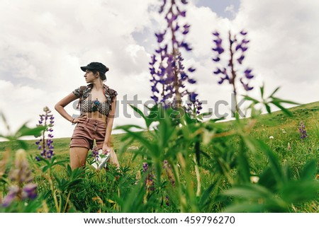 stylish hipster woman traveler standing among wildflowers and  lupin in mountains, travel and summer adventure concept, unusual view - stock photo