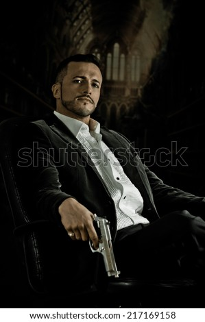 Stylish hispanic young handsome man model mobster spy hitman killer sitting in a chair holding a gun over dark background - stock photo
