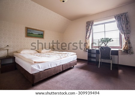 Stylish hotel room with double bed and desk