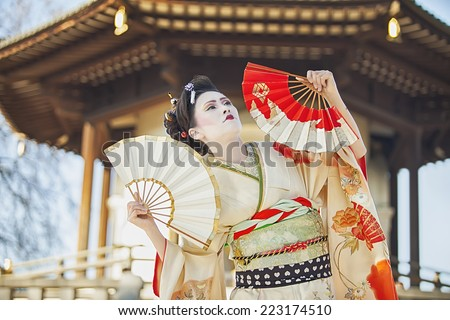 stylish japanese woman dancing with fans against Peace Pagoda in Battersea Park in London - stock photo
