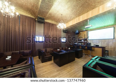 Stylish karaoke bar with leather armchairs and many screens. - stock photo