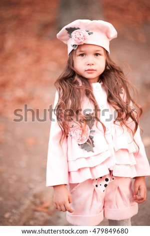 Stylish kid girl 3-4 year old wearing winter jacket, shorts and hat outdoors. Looking at camera. Childhood.