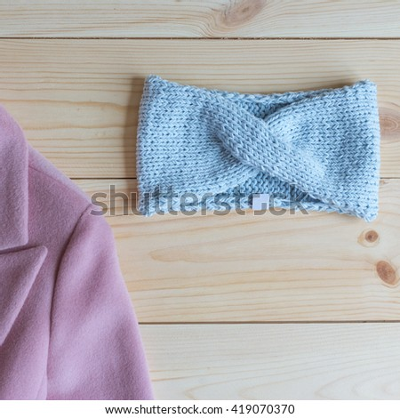 stylish knitted headband on a wooden table