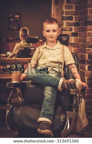 Stylish little boy in a barber shop - stock photo