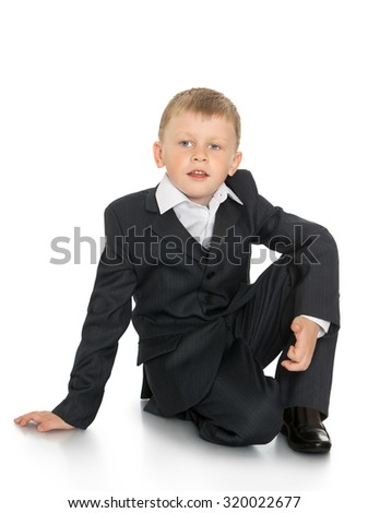 Stylish little boy in a suit sat down on the floor-Isolated on white background