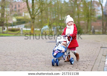 Stylish little child, cute blonde toddler girl, wearing beautiful red coat playing role game pushing stroller with toy outdoors in the city park - stock photo