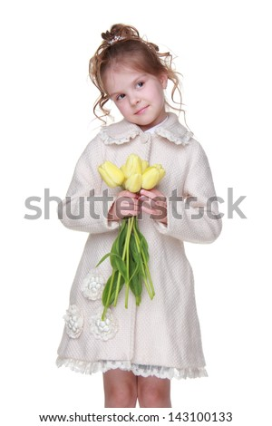 Stylish little girl wearing fashion coat and holding lovely yellow tulips on Holiday theme/Smiley girl with nice hairstyle