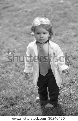 Stylish little serious boy child with curly hair in unbuttoned shirt necktie and trausers standing barefoot on fresh grass yard sunny day outdoor on natural background black and white, vertical photo - stock photo