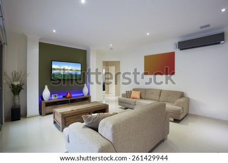 Stylish living area with flat screen TV and air conditioning - stock photo
