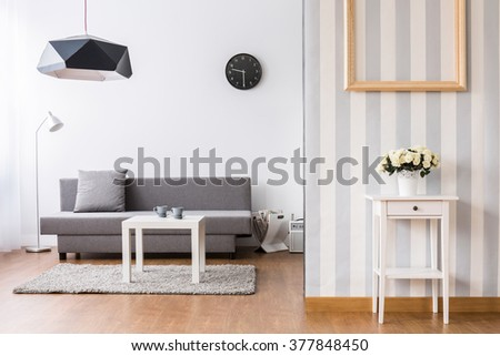 Stylish living room with grey sofa and small coffee table. Light interior with flooring and decorative wallpaper. - stock photo